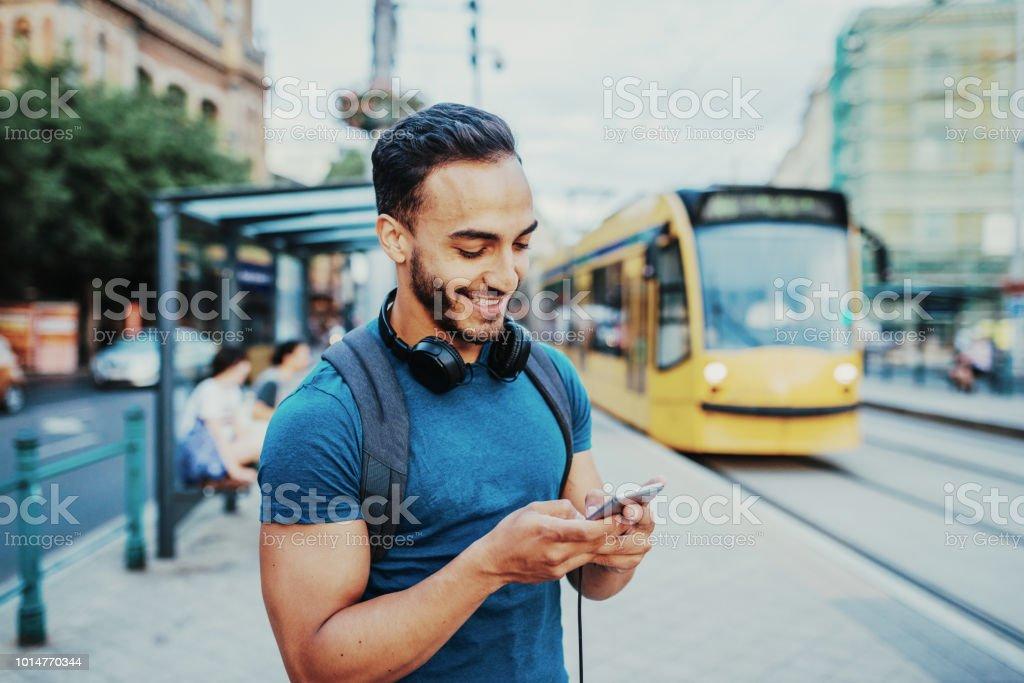 Jungunternehmer mit mobile app um zu sehen, die Straßenbahn-Zeitplan – Foto