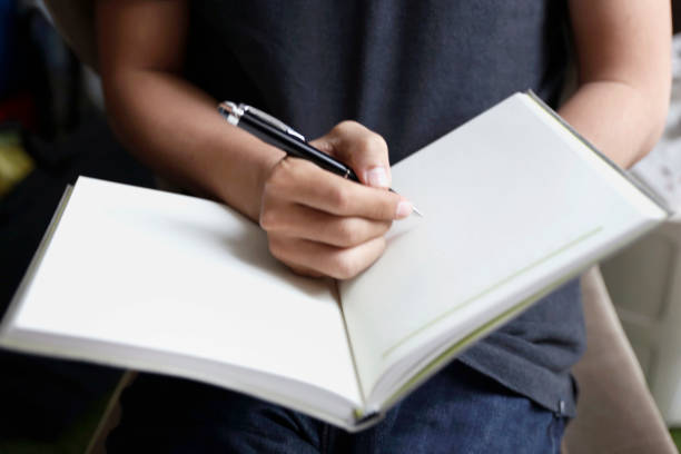 Young entrepreneur writing business ideas on notebook stock photo