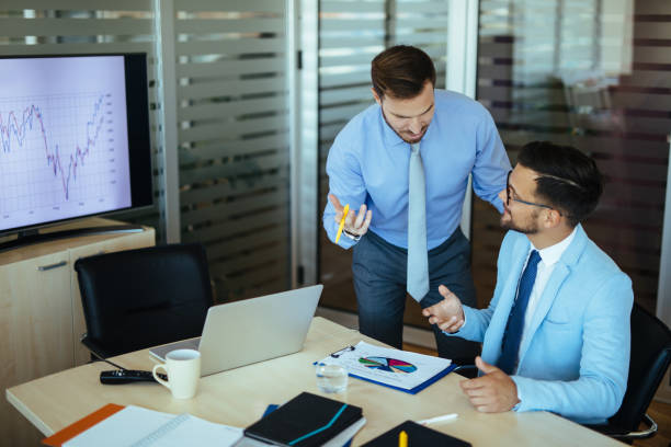 Young entrepreneurs analyzing business chart in the office stock photo