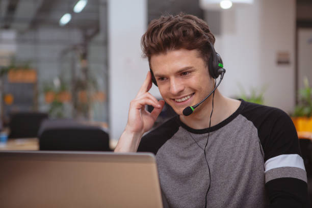Young entrepreneurs working at the office Young handsome man working at call center, wearing headset with microphone, copy space. Friendly male customer support operator answering callers, typing on laptop bingo caller stock pictures, royalty-free photos & images