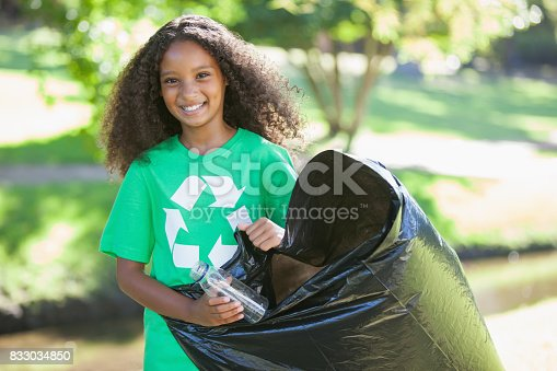 istock Young environmental activist smiling at the camera picking up trash 833034850