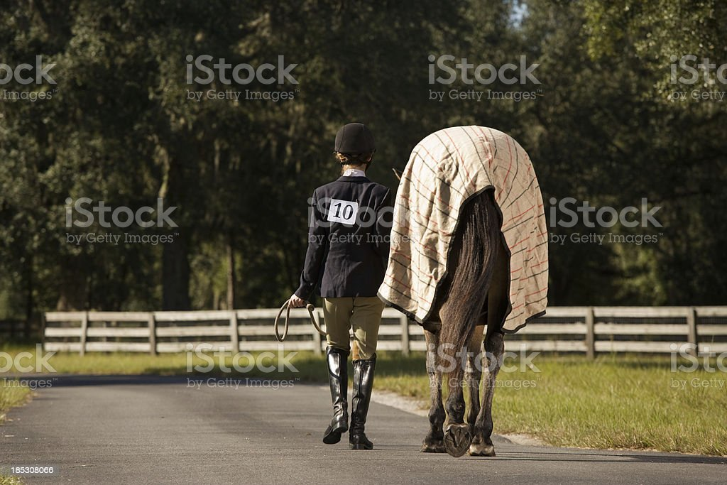 Young Equestrian walking with horse stock photo