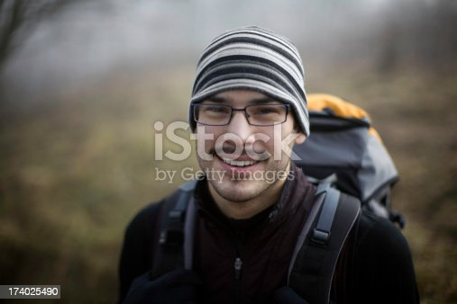 A smiling young Alaskan native on a backpacking trip.  Very shallow depth of field.  Horizontal with copy space.