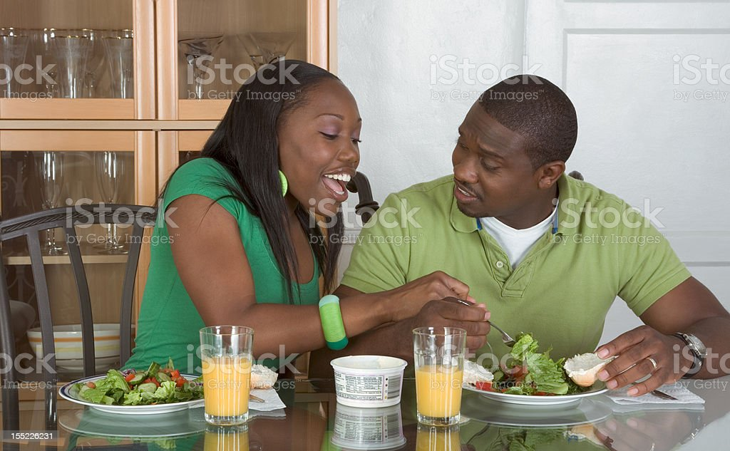 Young ethnic couple by table eating breakfast royalty-free stock photo