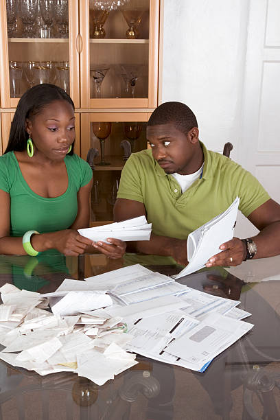 Young ethnic couple by table overwhelmed with bills. stock photo