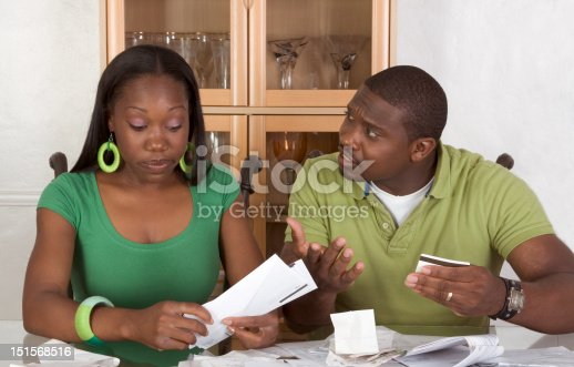 istock Young ethnic couple by table overwhelmed with bills 151568516