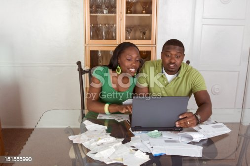istock Young ethnic couple paying bills over internet 151555990