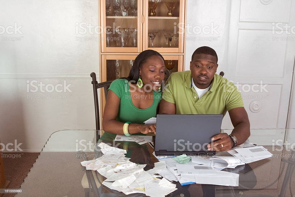 Young ethnic couple paying bills over internet stock photo