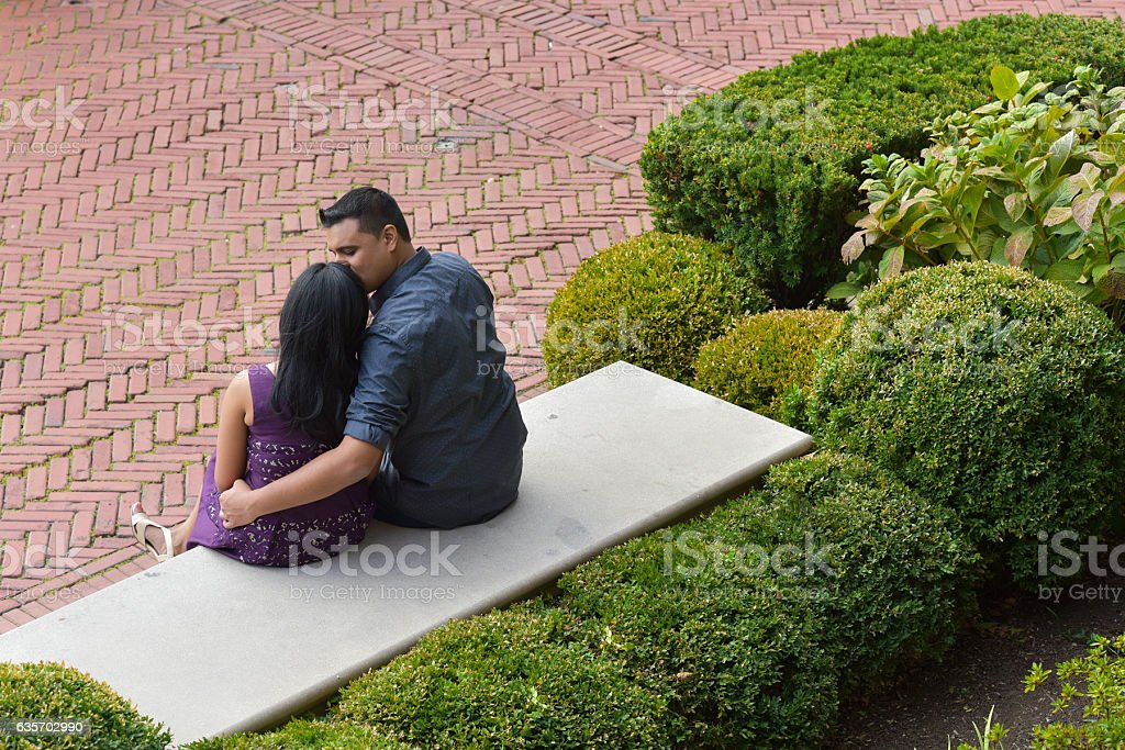 Young ethnic couple sitting on a bench royalty-free stock photo