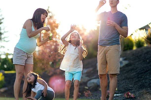 young ethnic family blowing bubbles in their backyard - schwangerschaftsaufnahmen stock-fotos und bilder