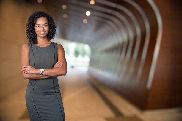 Young Ethnic Female Businesswoman A young confident latin or african american businesswoman stands with arms crossed smiling into the camera.  She is wearing a grey dress and is standing in a corporate office hallway or foyer. spokesperson stock pictures, royalty-free photos & images