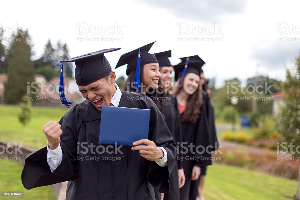 Young ethnic male celebrates after receiving his diploma stock photo