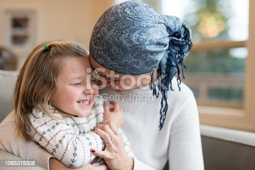 A beautiful young ethnic woman with cancer holds her preschool-age daughter in her lap by their living window. She is playfully bumping foreheads with her and they are both smiling. Mom is wearing a headscarf.