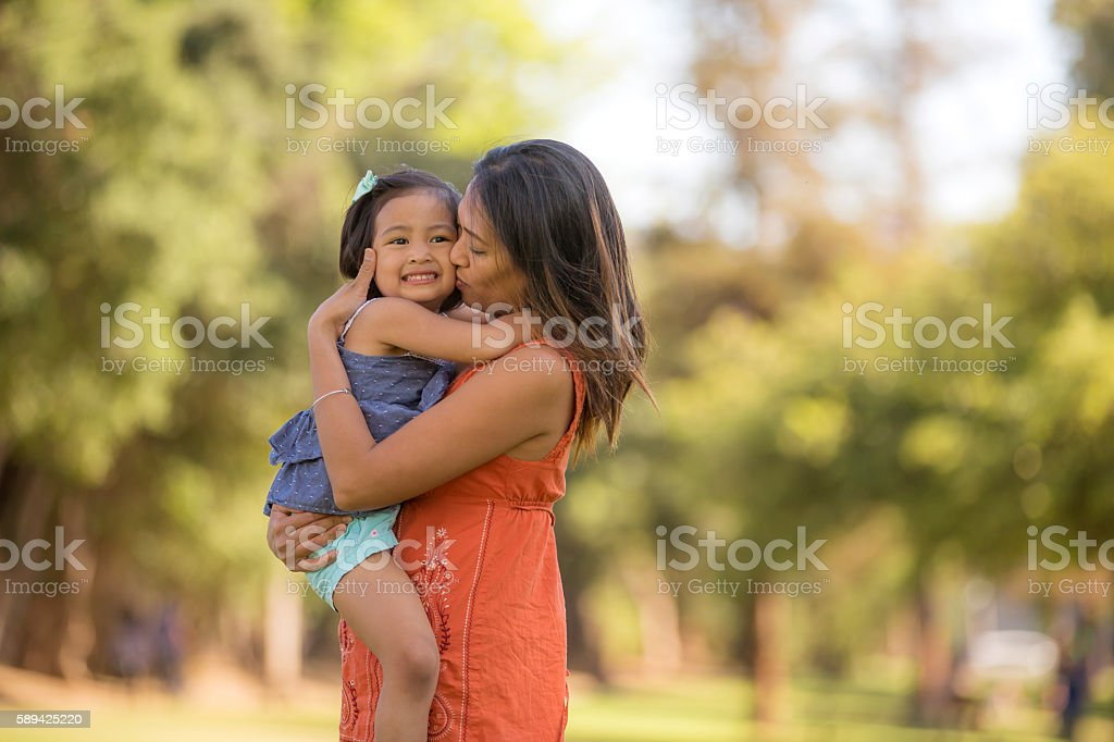 Young ethnic mother embracing her toddler girl outdoors stock photo