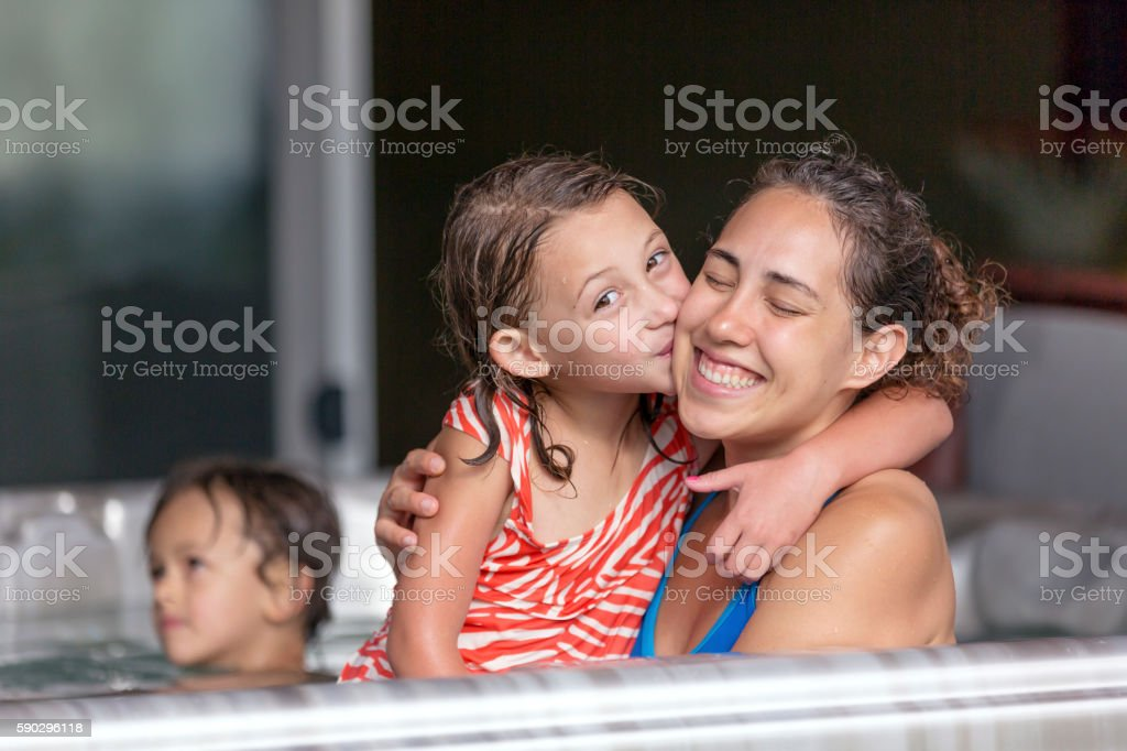Young ethnic mother posing with her daughter in a jacuzzi royaltyfri bildbanksbilder