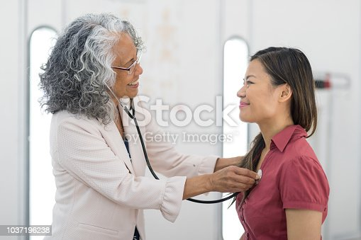 An attractive young ethnic woman sits on the examination table while her female doctor does some diagnostic tests with a stethoscope.