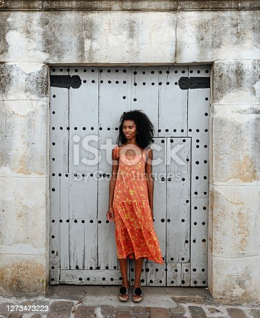 Full length of young African American female in colorful sundress standing against shabby door of old stone building on city street