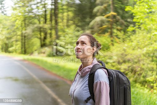 An ethnic woman in her early 30s walks along a country road on a summer afternoon. She has stopped to admire the view and is looking up to camera-left with a big smile.