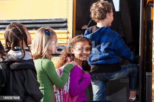 Four children of various ethnicities are boarding a yellow school bus.  A young girl with long curly hair wearing violet sweater is smiling.  A boy is in front climbing the steps to board the bus.