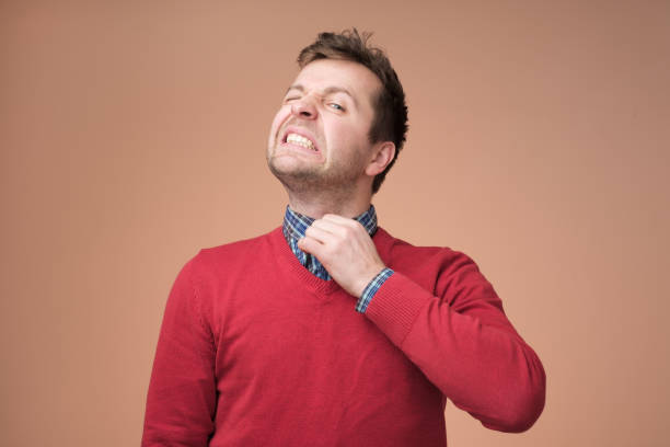 Young europeam man in red sweater feeeling uncomfortable. Young europeam man in red sweater feeeling uncomfortable. Colar is tight and stuffy and he tries to expand the collar to make a breath. Hate office clothes embarrassment stock pictures, royalty-free photos & images