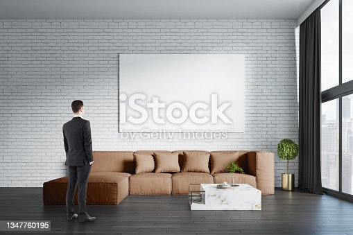 istock Young european businessman standing in modern living room interior with big couch, empty white mock up banner on brick wall, other pieces of furniture, curtain, window with daylight and city view. 1347760195