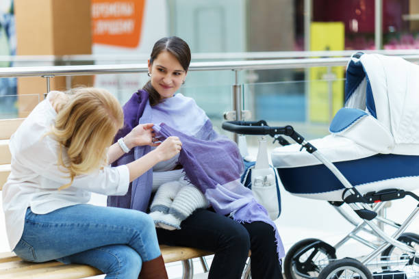 young european gay couple or friends women with baby sitting on a bench close to white baby carriage while one of them spying on breastfeeding son at public place shopping mall - mom spying stock photos and pictures