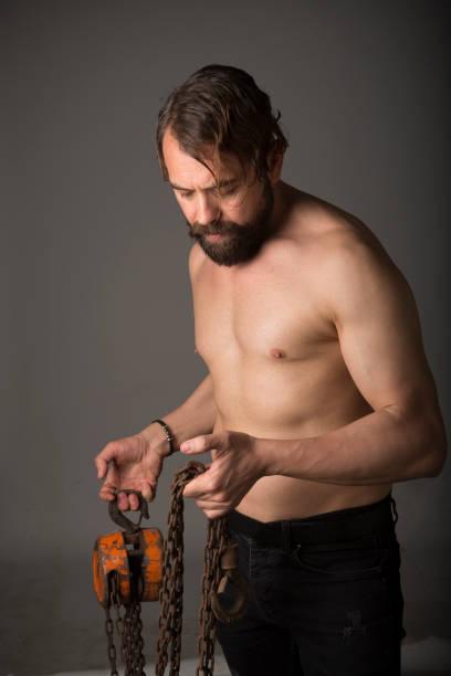 junge europäische Mann mit Bart posiert mit Ketten im Studio in Istanbul Türkei – Foto