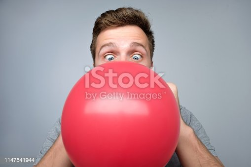 Young european man blowing up a red balloon preparing for party on gray background