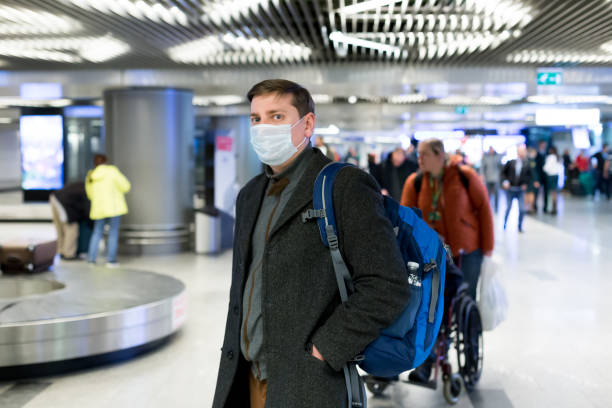 young european man in gray coat, protective disposable medical mask in airport. afraid of dangerous n-cov 2019 influenza coronavirus mutated and spreading in china. blue backpack, suitcase on wheels - covid mask stock pictures, royalty-free photos & images