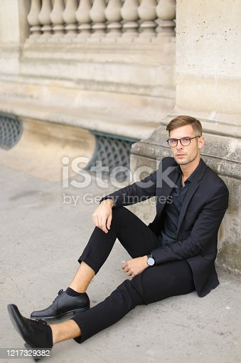 665586146 istock photo Young european man sitting on sidewalk ground and wearing black suit 1217329382