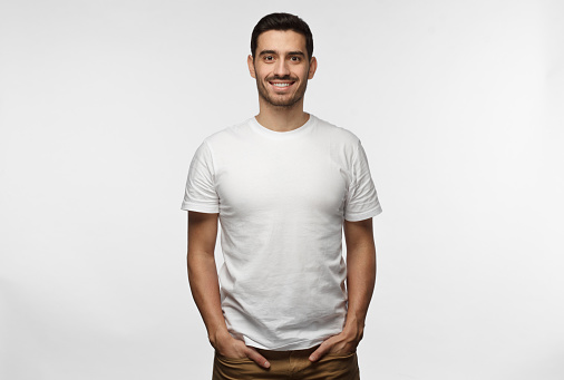 istock Young european man standing with hands in pockets, wearing blank white tshirt with copy space for your logo or text, isolated on grey background 1022174596