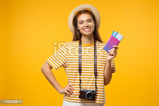 Young European woman feeling joy of coming trip with airtickets and passport in hand, isolated on yellow background