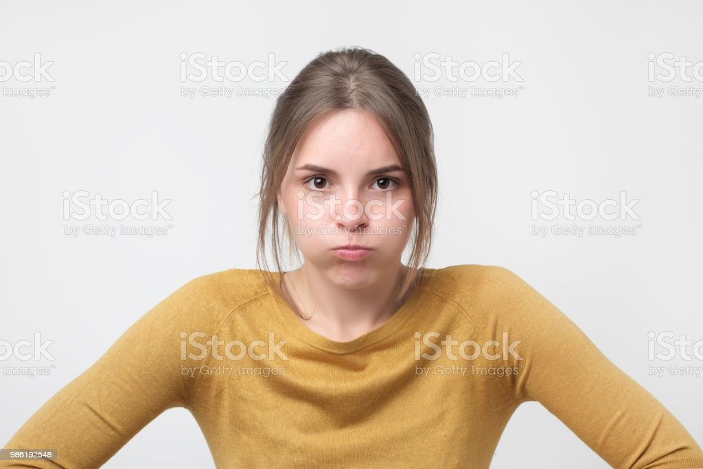 Young european woman in yellow sweater looking with offended look, being dissatisfied with something stock photo