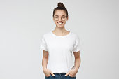 istock Young european woman standing with hands in pockets, wearing blank white tshirt with copy space for your logo or text, isolated on grey background 1001506012