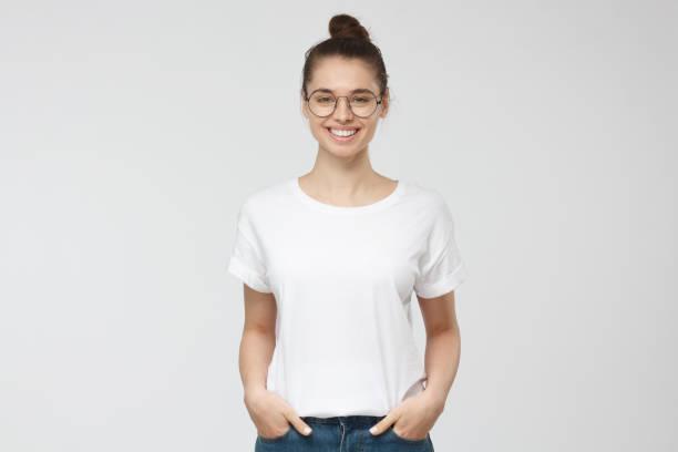 젊은 유럽 여자 주머니에 손을 함께 서 있는, 귀하의 로고 또는 텍스트를 회색 배경에 고립에 대 한 복사 공간을 가진 빈 흰색 tshirt 입고 - 백인종 뉴스 사진 이미지