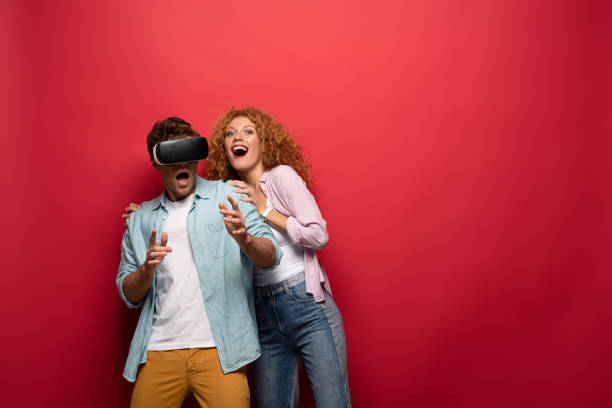 young excited couple using virtual reality headset, isolated on red - vr red background imagens e fotografias de stock