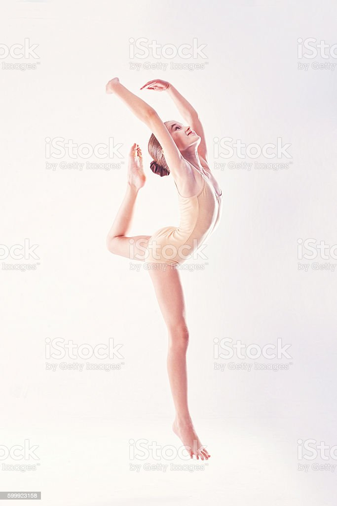 Young excited girl jumping in the studio stock photo