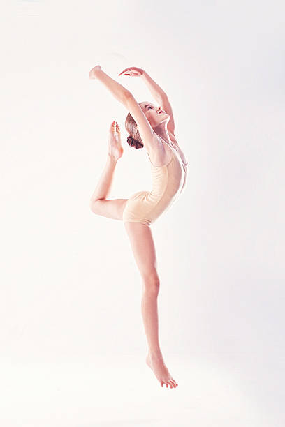 young excited girl jumping in the studio - kinder ballerinas stock-fotos und bilder