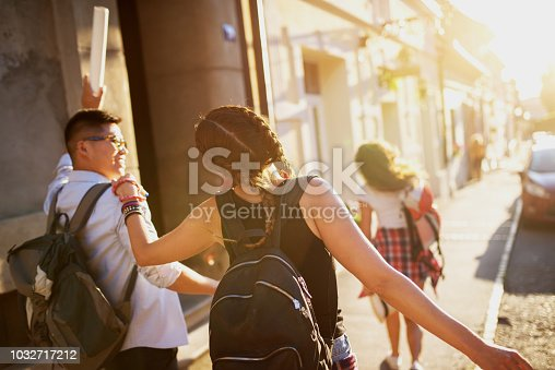 503545320 istock photo Young excited student tourists walking in a city streets and having fun on a hot summer day. 1032717212