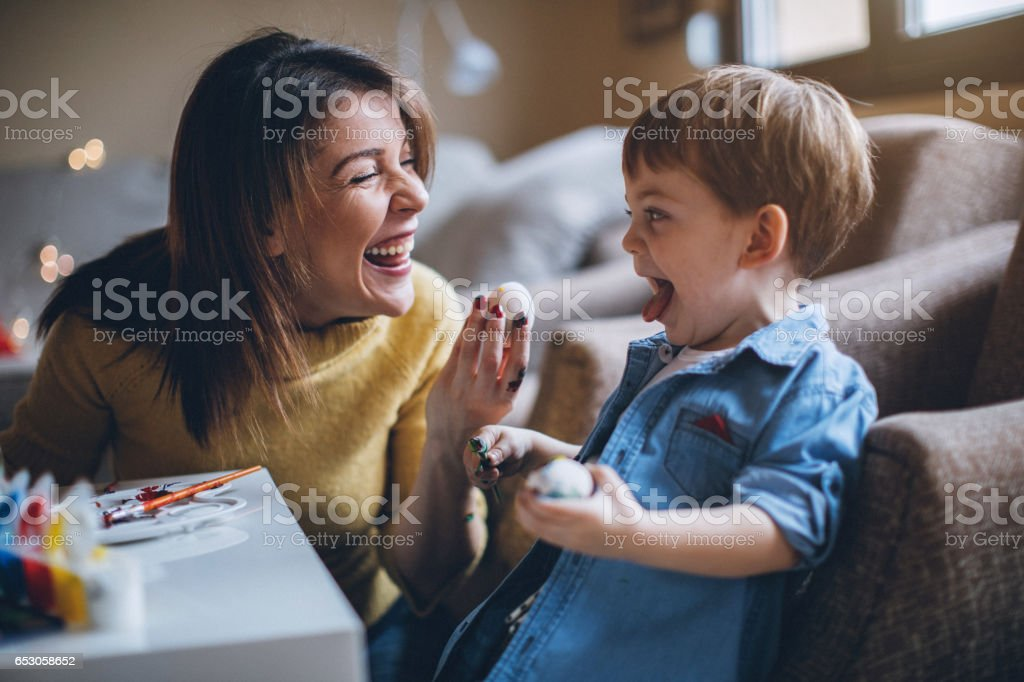Young excited woman giving her little son Easter egg stock photo