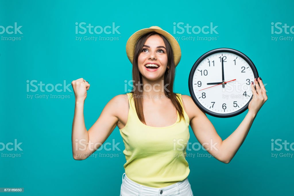 Young excited woman holding a clock showing nearly 9 with happy victory emotions on green background stock photo