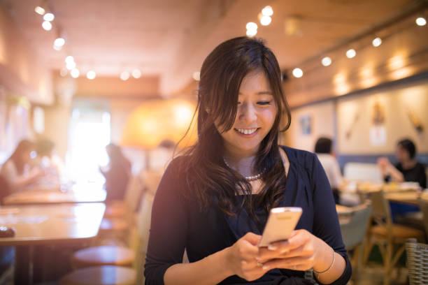 年輕的執行董事,在咖啡廳的業務會議期間輸入消息 - 僅一名中年女子 個照片及圖片檔