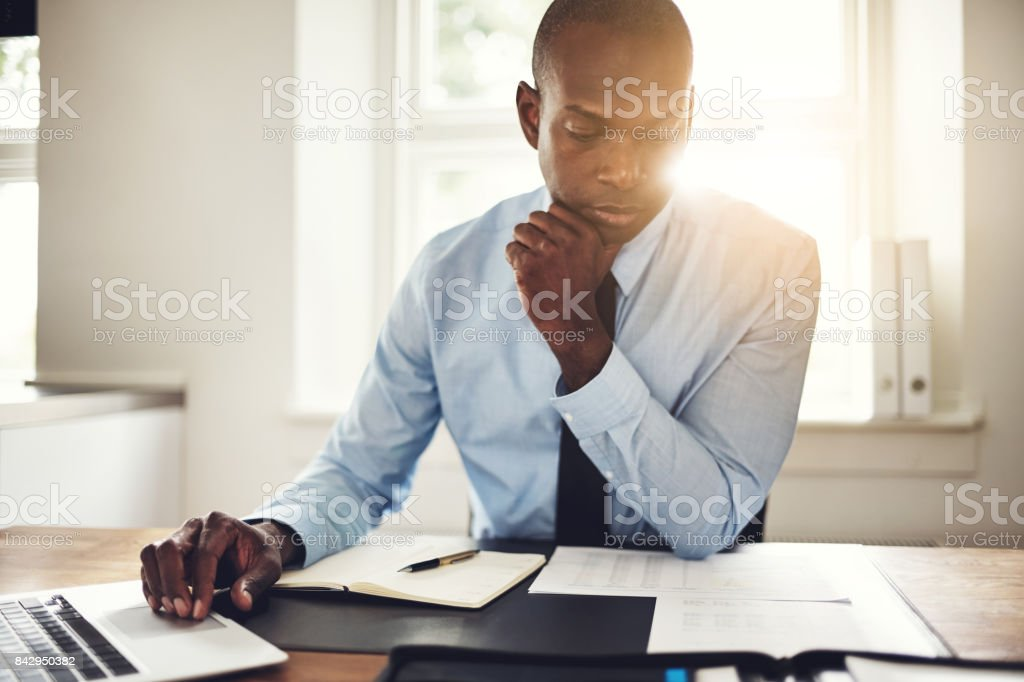 Young executive reading paperwork and using a laptop stock photo