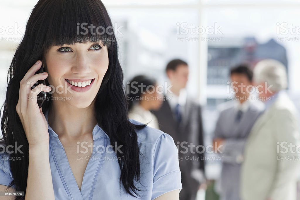Young executive smiling phone and accompanied by her team royalty-free stock photo