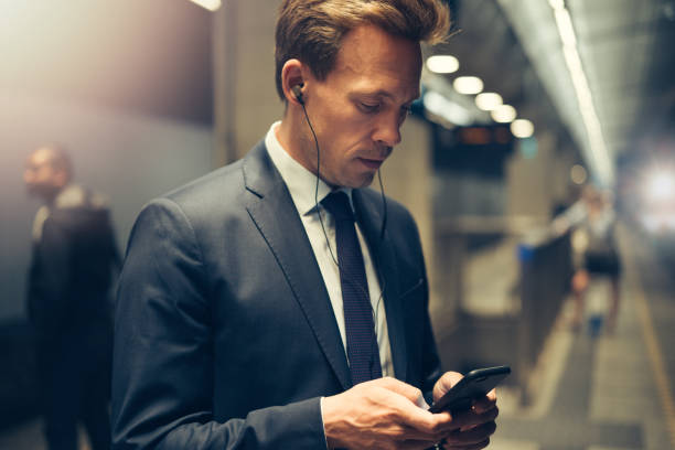 Young executive standing on a subway platform reading text messages Young businessman wearing earphones and sending text messages on his cellphone while standing on a subway platform during his morning commute mp3 player stock pictures, royalty-free photos & images