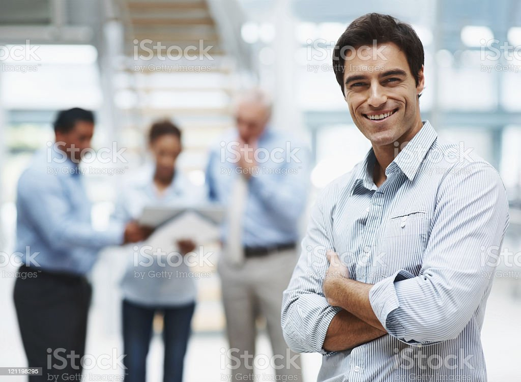 Young executive standing with team mates discussing at the back royalty-free stock photo