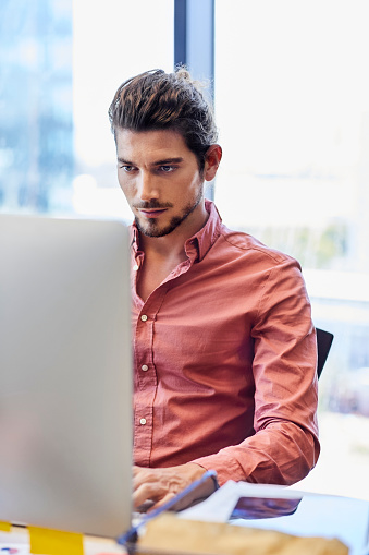 Young executive using computer at creative office. Handsome businessman is sitting at desk against window. He is in smart casuals.
