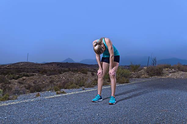Junge sportliche Frau Laufen erschöpft im Freien auf Asphaltstraße Atmen – Foto