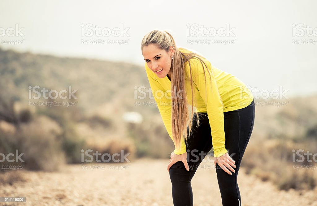 young exhausted sport woman running outdoors on dirty road breathing stock photo