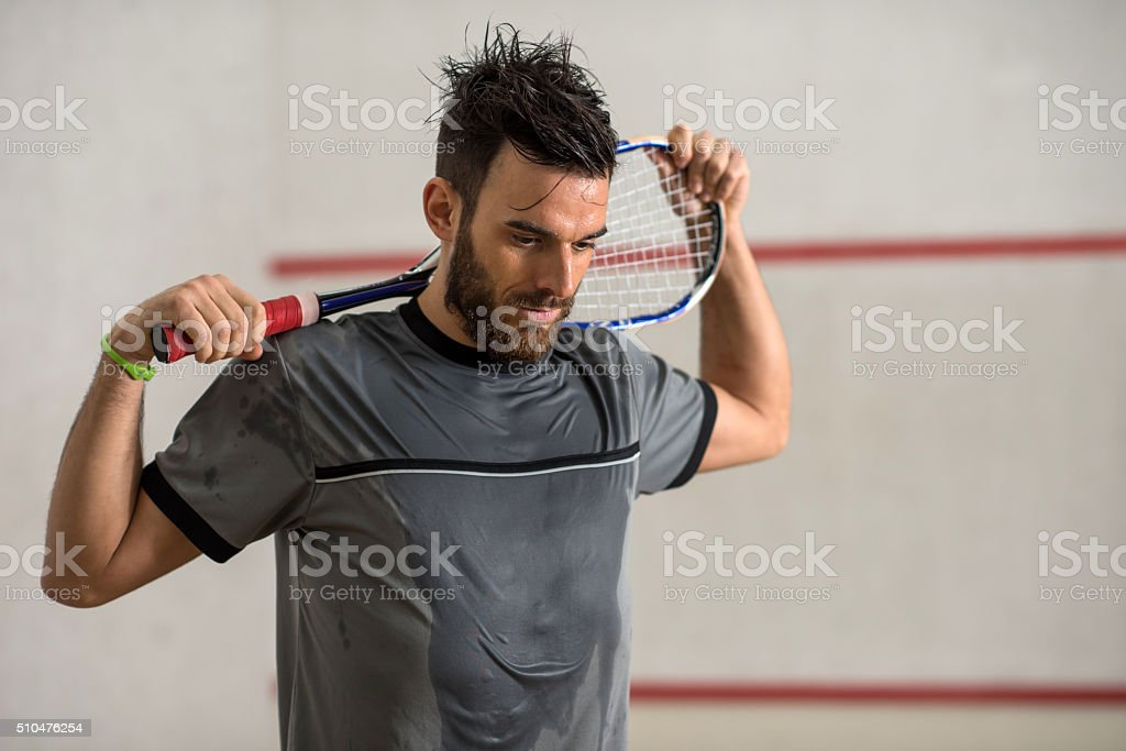 Young exhausted squash player with a racket. stock photo